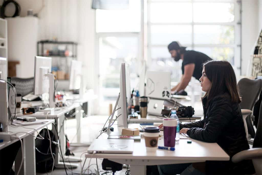 A woman working at her desktop in a busy open office.